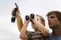 Father and son using binoculars, man pointing skyward