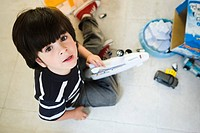 Little boy sitting on floor playing with toys, looking up at camera
