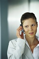 Businesswoman using cell phone, glancing sideways