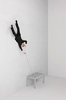 Businessman floating upside down holding landline phone, cutting cord with scissors