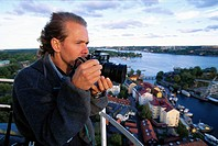 A man with a camera with a view over Stockholm Sweden.