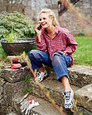 A woman sitting in a garden talking in a cellphone Sweden.