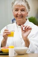 An elderly woman taking her medicine Sweden.
