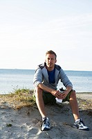 A man resting after jogging on the beach Malmo Sweden.