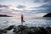 Young woman doing yoga on rocks at sunset in front of ocean surf at Playas del Coco, Costa Rica