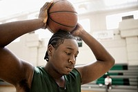 African basketball player holding ball and looking down in gym