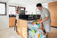 Japanese man doing dishes while woman uses laptop