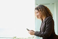 Hispanic woman text messaging on balcony