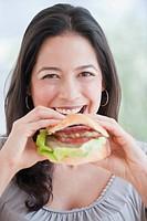 Hispanic woman eating hamburger
