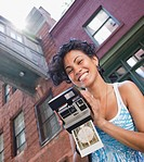 Mixed race woman holding instant camera