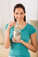 Hispanic woman putting money in jar