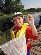 a 5 or 6 year old boy with a frog that he caught in a dip net at a lake