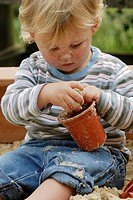 Small boy playing with a flowerpot in a sandpit