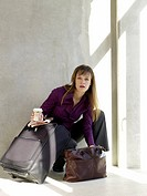 Business woman with baggage holding a cup of coffee (thumbnail)