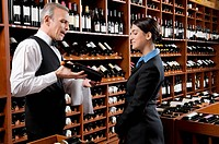 Waiter showing a wine bottle to a businesswoman