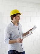 Man wearing a helmet with construction plans