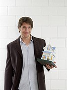 Mann holding a small model house (thumbnail)