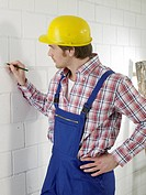 Construction worker is marking with a pencil on the wall (thumbnail)