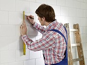 Man wearing work wear is marking on wall