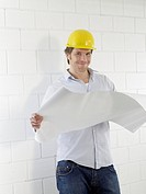 Man wearing helmet with construction plans (thumbnail)