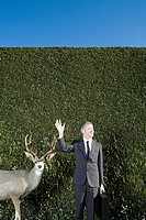 Waving businessman with deer
