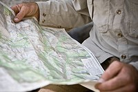Mid section view of a hiker holding a map