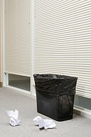 Wastepaper bin in office with screwed up paper next to it
