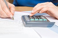 Person with calculator and forms