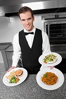 Waiter holding plates of foods
