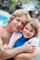 Portrait of a man hugging his son at the poolside