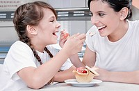 Girl and a teenage girl feeding ice cream to each other