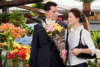 Couple with a bouquet of flowers in a florist shop