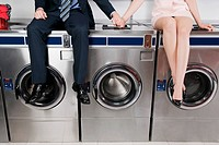 Couple holding hands and sitting on washing machines