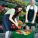 Man holding a wheelbarrow and a woman putting potted plant in it