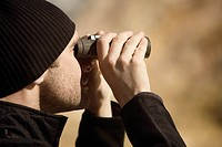 Man looking through binoculars, Mammoth Hot Springs, Yellowstone National Park, Wyoming, USA