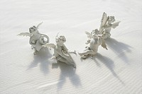 Angel figurines with musical instruments on white sand