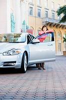 Woman leaning against a car door and smiling, Biltmore Hotel, Coral Gables, Florida, USA