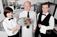 Two waiters and a waitress standing in the kitchen