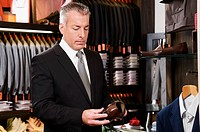 Businessman selecting shoes in a clothing store