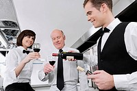 Waiter pouring wine into the glasses of his colleagues