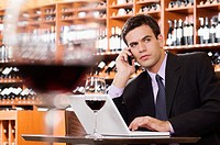 Businessman talking on a mobile phone and using a laptop in a bar