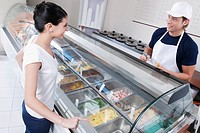 Sales clerk attending a customer in an ice cream parlor