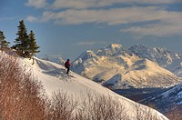 Man snowshoeing above Arctic Valley with Chugach Mountains in the background, Southcentral Alaska