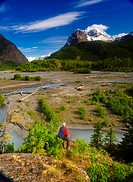 Hiker stands on a rock outcrop overlooking Eagle River, Chugach State Park, Southcentral Alaska, Summer