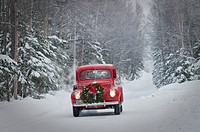 Man driving a vintage 1941 Ford pickup with a Christmas wreath on the front during Winter in Southcentral, Alaska
