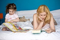 mother and daughter reading book on the bed