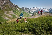 Visitors hiking on ridge in Kenai Mountains during during helicopter flightseeing tour in Kachemak Bay State Park near Homer, Kenai Penninsula, Alaska...