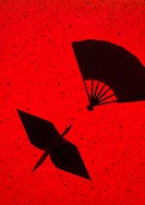 Silhouetted paper crane and fan against red background