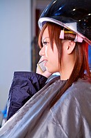 Young woman sitting under hair dryer and on the phone, Hair Salon