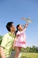 Family, father and daughter playing toy airplane outdoors